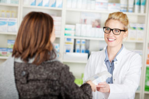 lächelnde apothekerin verkauft medikament